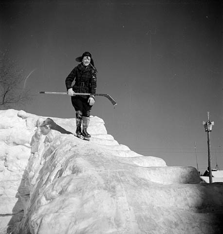 Boy skating down an ice-covered log dump on Sloe Lake, Quebec, 1943. National Film Board of Canada.