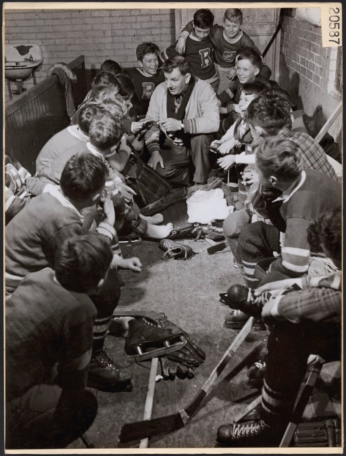 A coach gives pointers to players of the Copper Cliff minor hockey league in the dressing room. March, 1946. National Film Board of Canada.